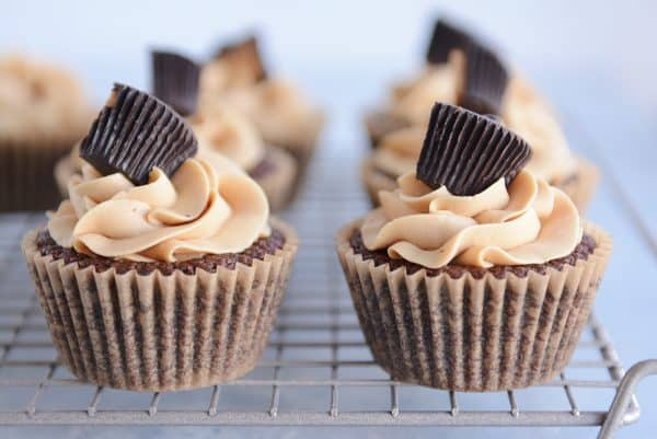 Side by side fudgy brownie cupcakes with the best peanut butter frosting and topped with a peanut butter cup.