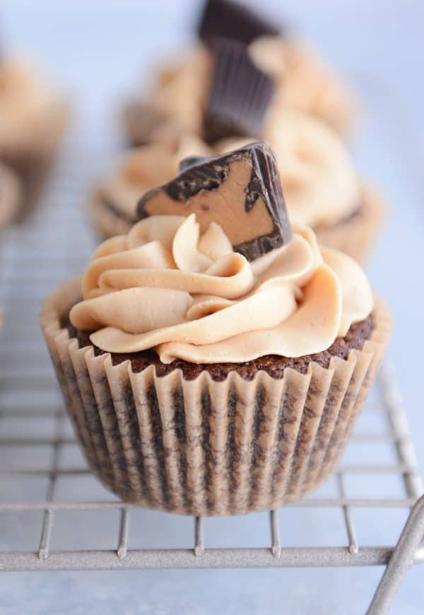 Fudgy brownie cupcake with the best peanut butter frosting swirled on top and garnished with half of a peanut butter cup.