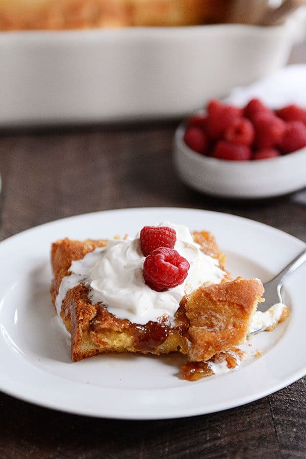 A fork taking a bite out of apiece of creme brulee french toast topped with whipped cream and raspberries.