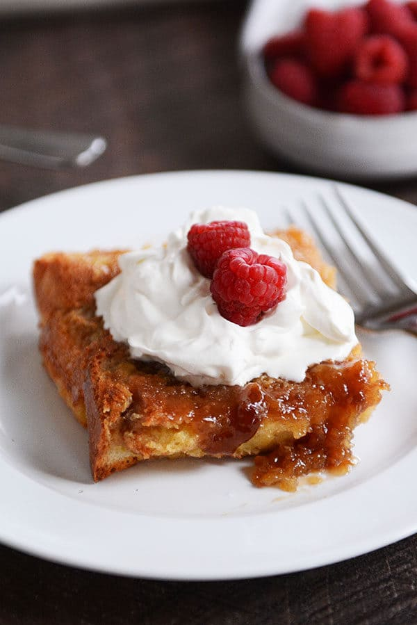 A piece of creme brulee french toast topped with whipped cream and rasperries.