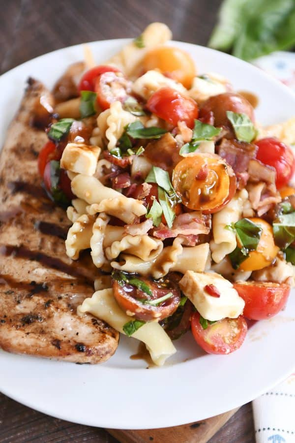 Close up of bruschetta chicken and bacon pasta on white plate.