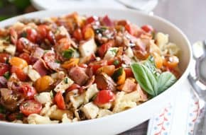 Bruschetta chicken and bacon pasta in large white serving bowl with fresh basil.