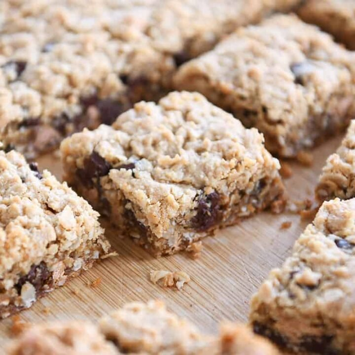 Slab of monster cookie bars cut into squares on wood board.