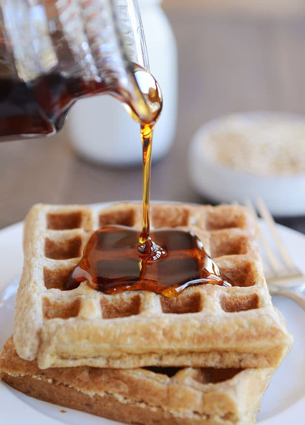Syrup being poured over two thick Belgian waffles.