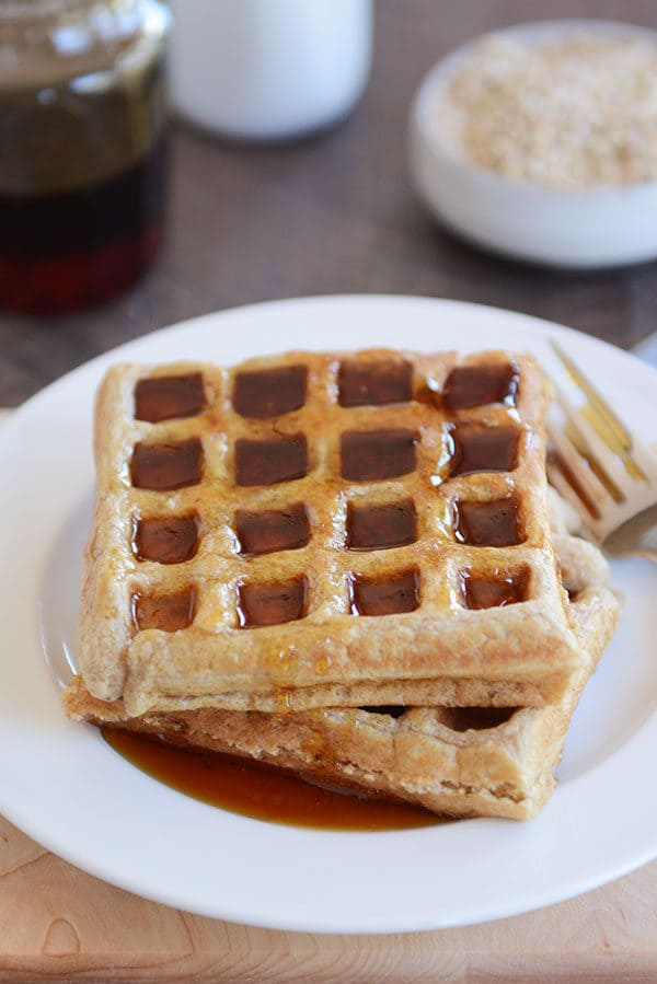 Two thick waffles covered in syrup on a white plate.
