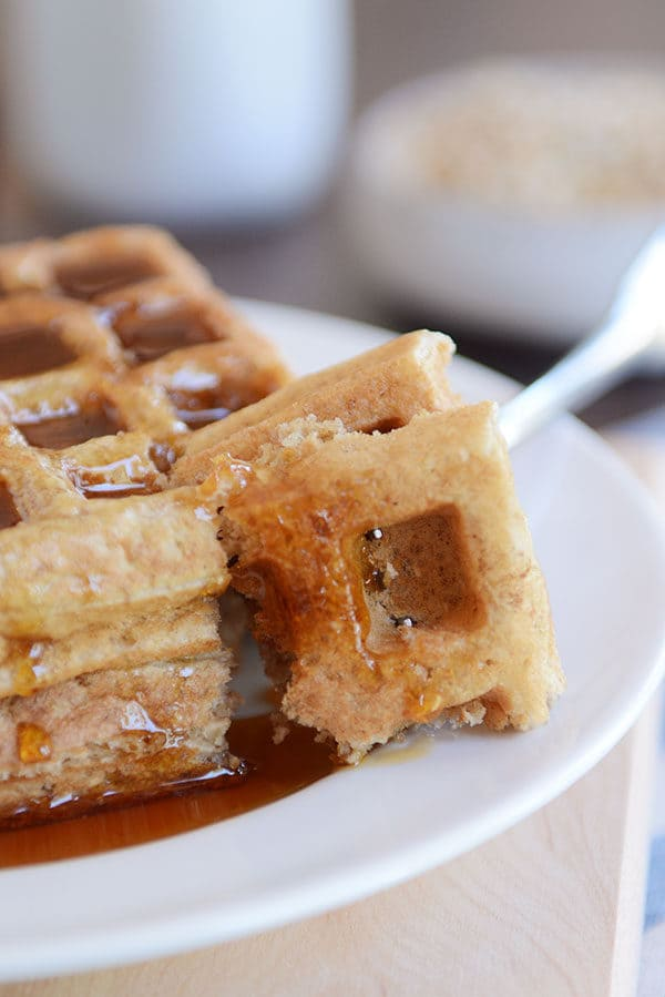 A fork taking a bite out of two thick syrupy waffles on a white plate.