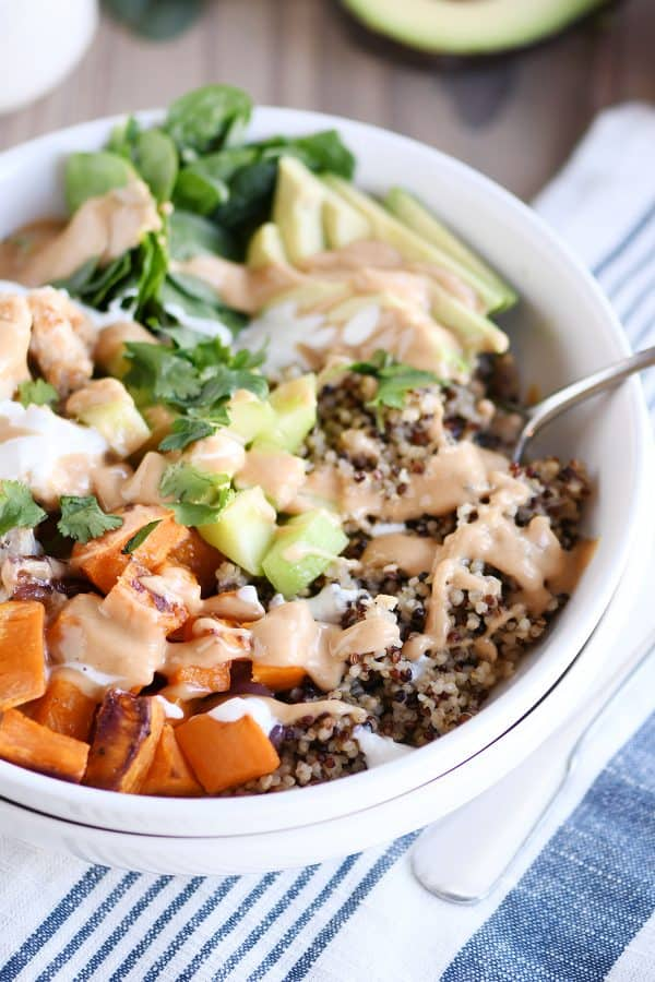 Assembled Buddha bowl recipe with peanut sauce in white bowl with fork.