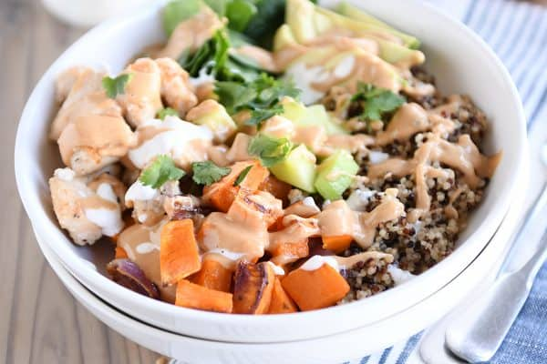 Assembled Buddha bowl recipe with peanut sauce in white bowl.
