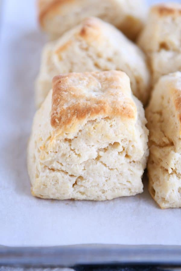 Several super flaky buttermilk biscuits on white platter.