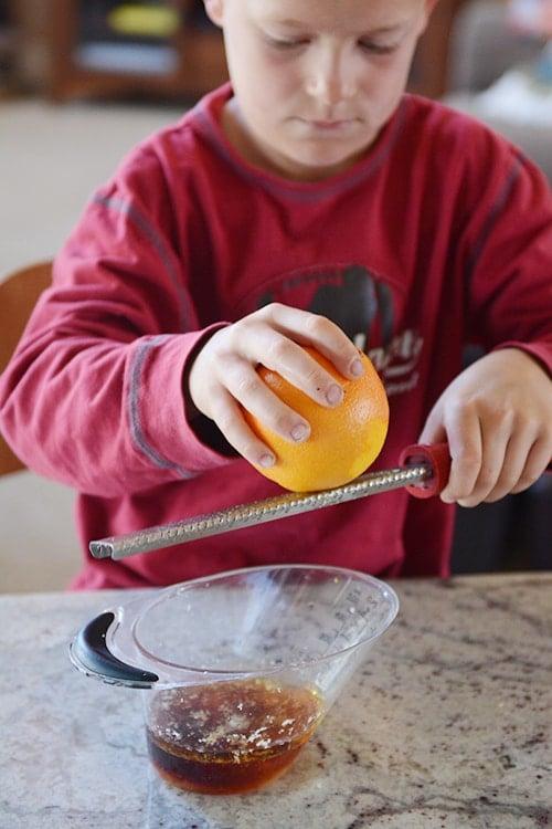 A little boy grating an orange over a microplane.