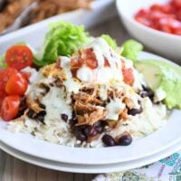 White plate with cilantro lime rice, black beans, sweet pork and toppings.