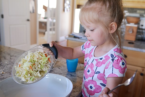 A little girl pouring shredded cabbage into a large white platter.