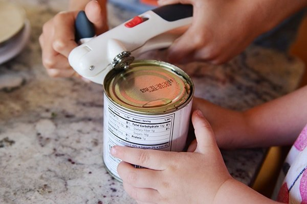 A can opener opening a can.