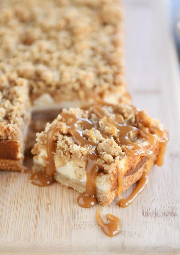 Slice of caramel apple cheesecake bars drizzled with caramel on wood cutting board.