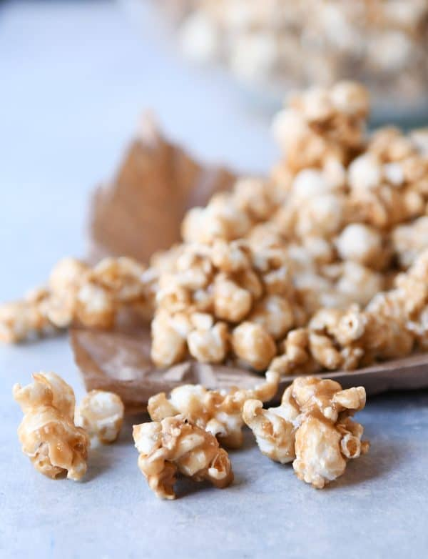 Soft and chewy caramel popcorn on brown paper bag.