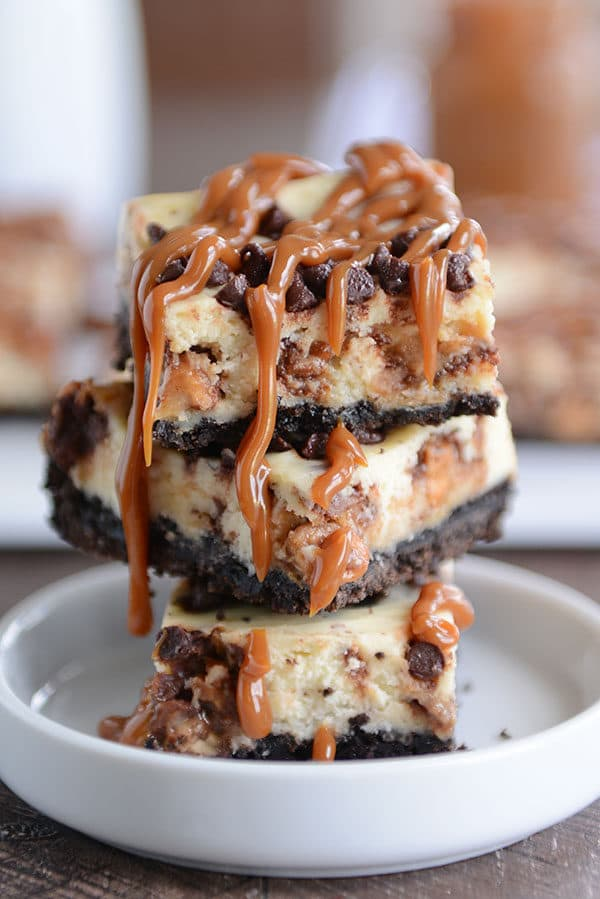 Stacked caramel cheesecake Oreo cheesecake bars in a white ramekin.