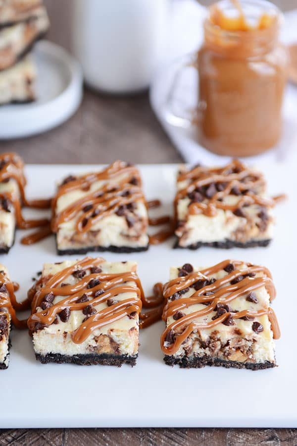 Snickers Oreo cheesecake bars topped with chocolate chips and caramel drizzle on a white platter.