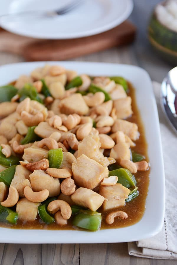 A white platter of saucy cashew chicken with large green pepper chunks mixed in.