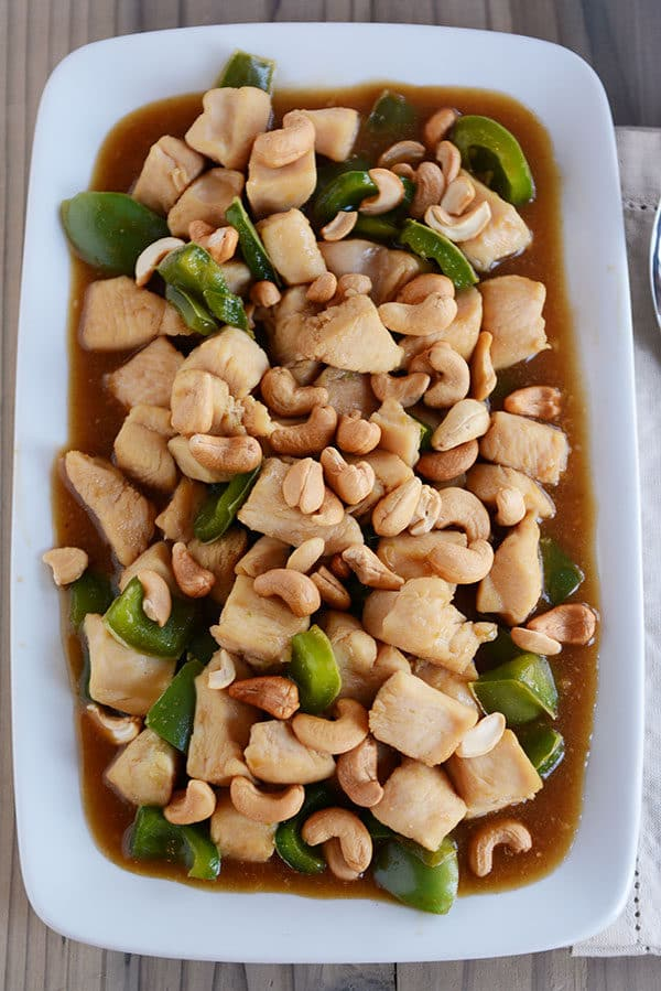 Top down view of a large white platter of chinese cashew chicken with sauce and green peppers.