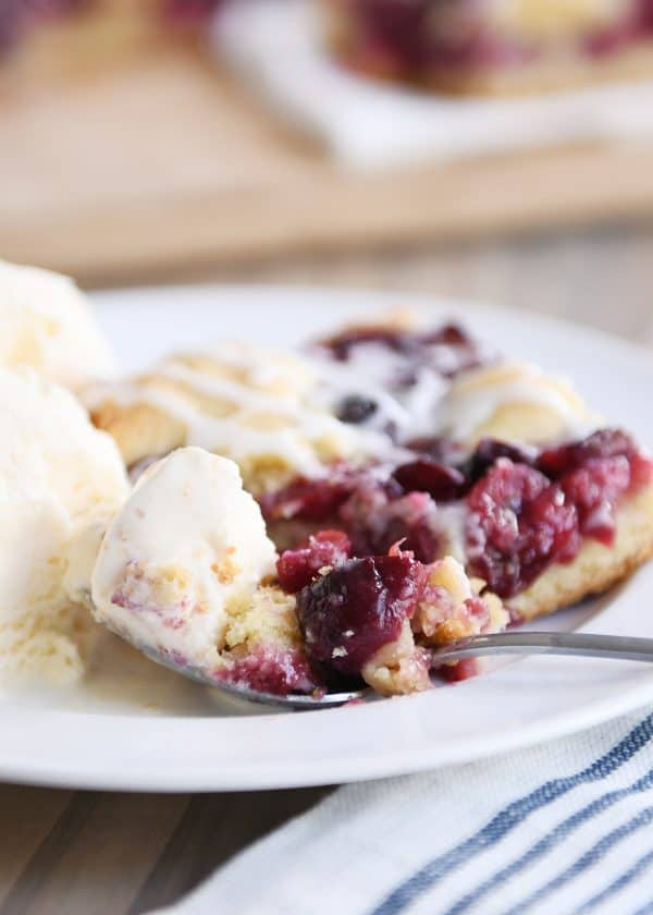 Cherry pie cookie bar on white plate with scoop of ice cream.
