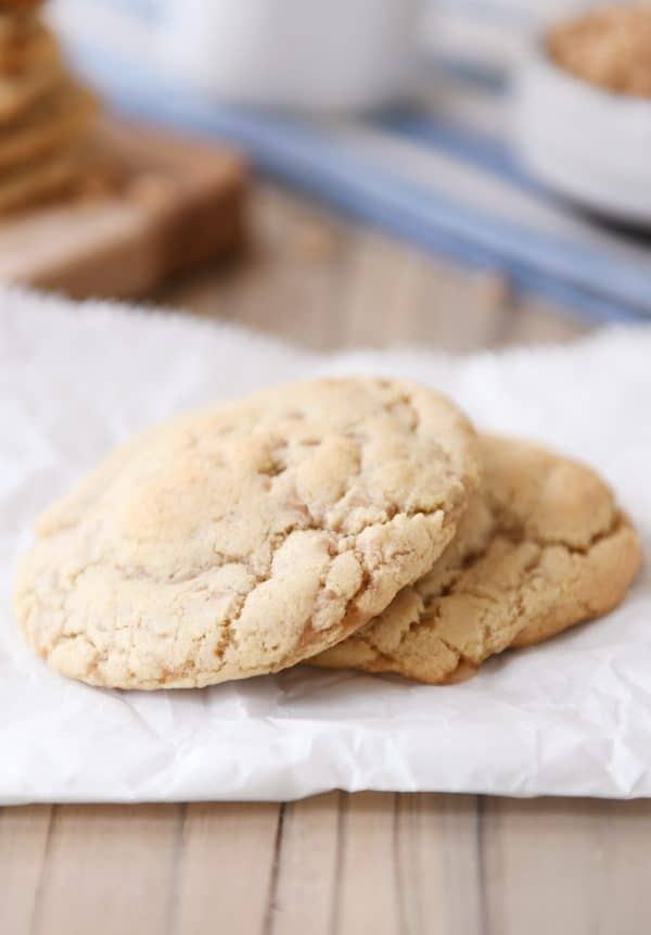 two thin toffee cookies stacked on a piece of parchment