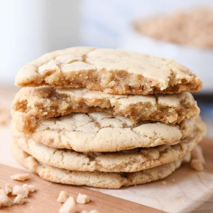 Stack of toffee cookies on wood cutting board with one cookie broken in half.