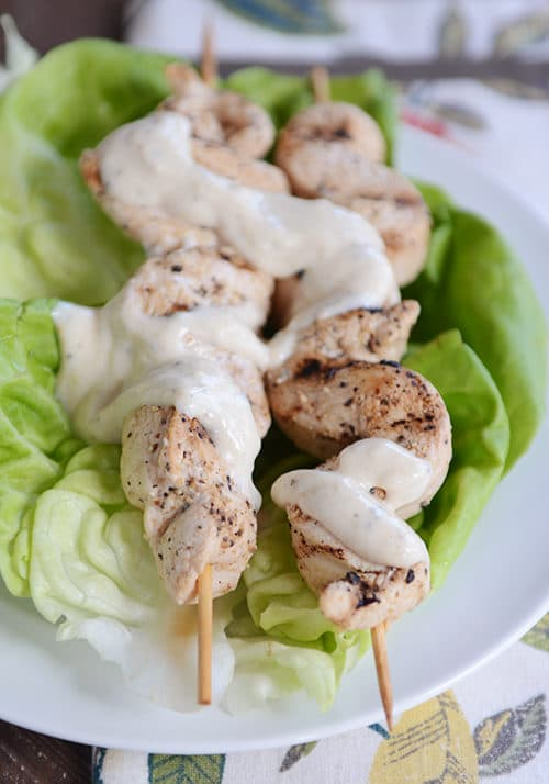 Two grilled chicken skewers drizzled with a yogurt hummus sauce.