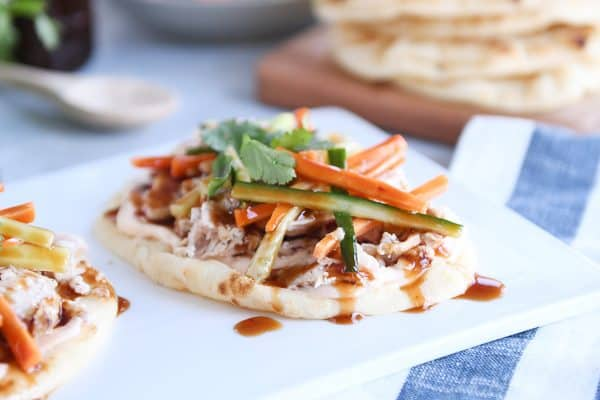 Chicken banh mi flatbread with pickled cucumbers and carrots on white platter.