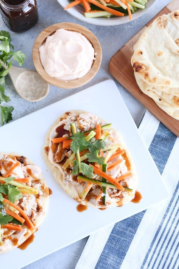 Top down view of Chicken banh mi flatbread with pickled cucumbers and carrots on white platter.