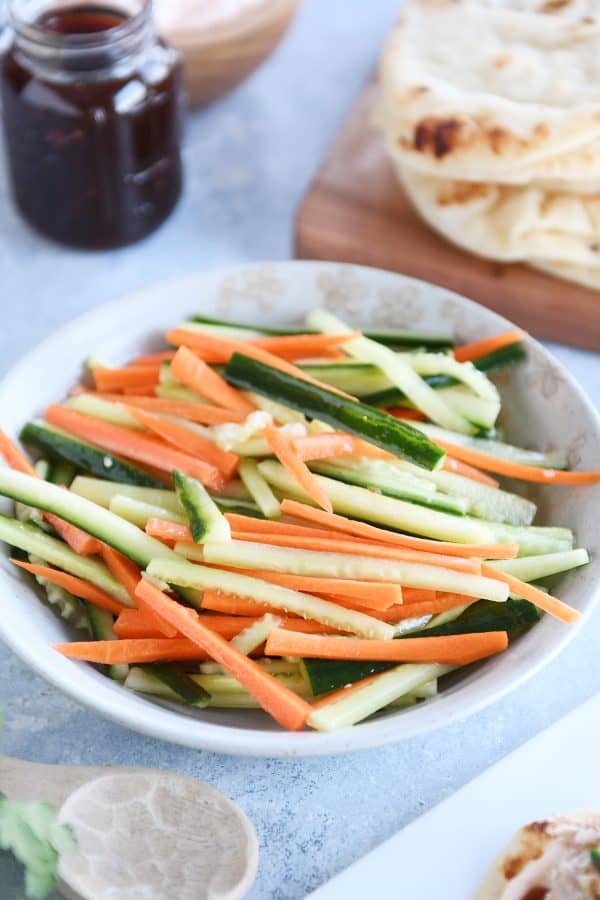 Tan bowl filled with pickled cucumber and carrot sticks.