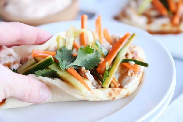 Folded chicken banh mi flatbread like a taco ready to eat on white plate.