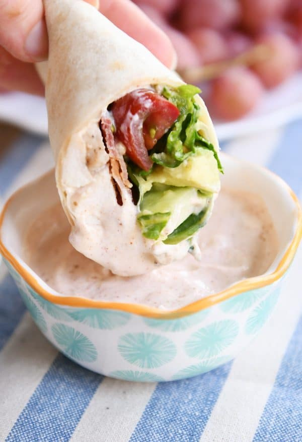 Dipping chicken BLT burritos in creamy dipping sauce.