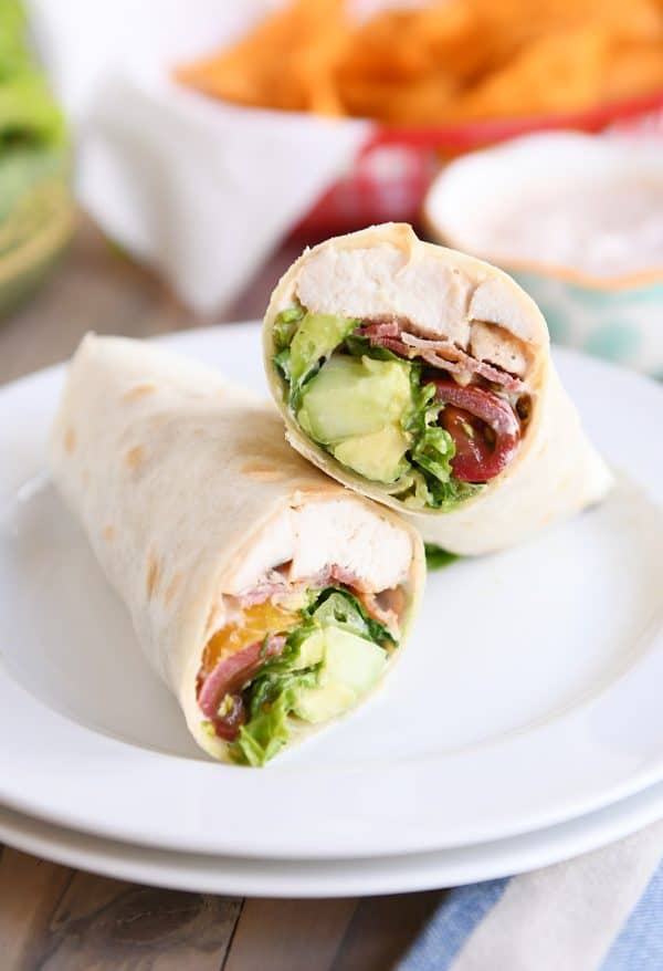 Chicken BLT burritos cut in half on white plate.