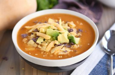 Chicken enchilada soup in tan bowl with brown stripe.