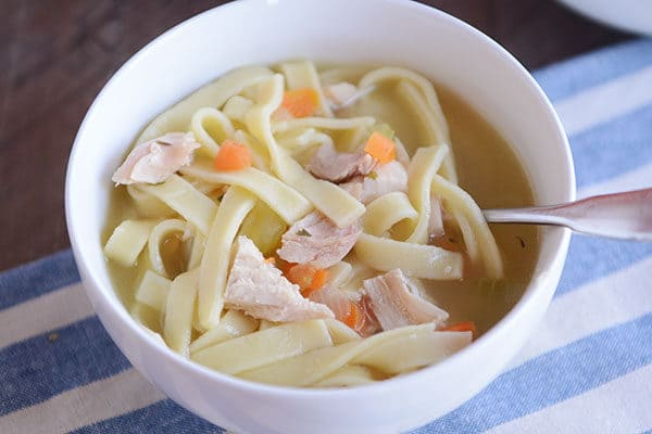A white bowl of chicken noodle soup with a spoon in the side.