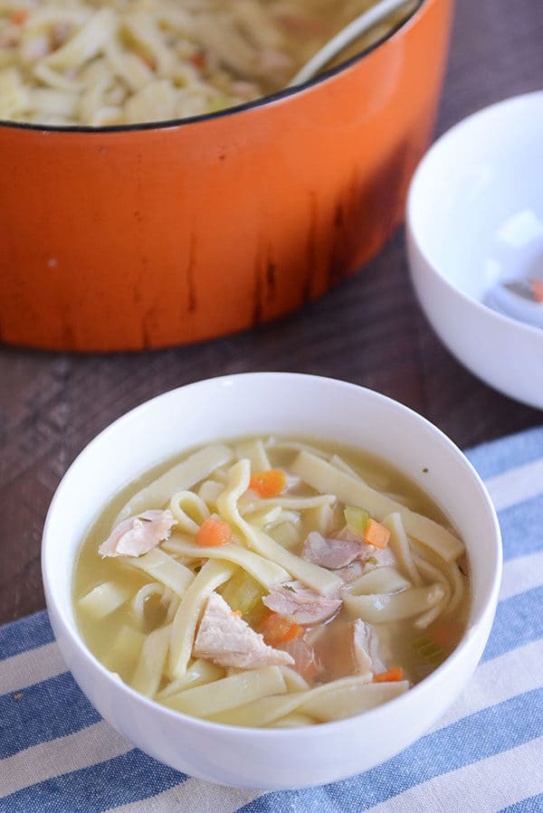 A white bowl of chicken noodle soup with a large pot of the soup behind it.