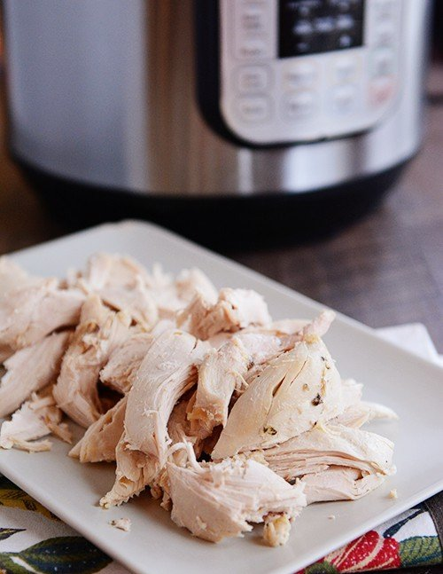 Cooked, shredded chicken on a white plate, in front of an Instant Pot.