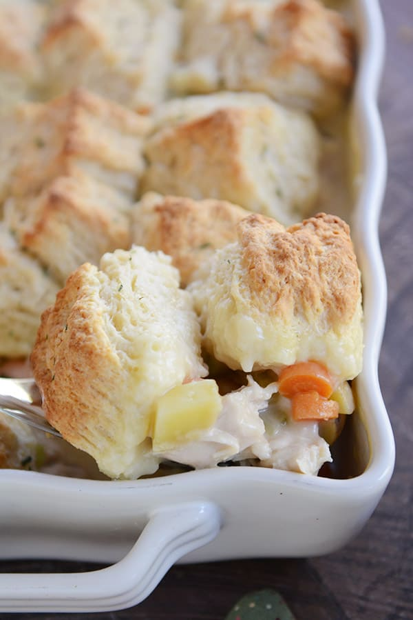 a white casserole dish of biscuit-topped chicken pot pie