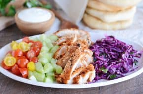 White platter with grilled chicken shawarma, cucumbers, tomatoes and cabbage slaw.