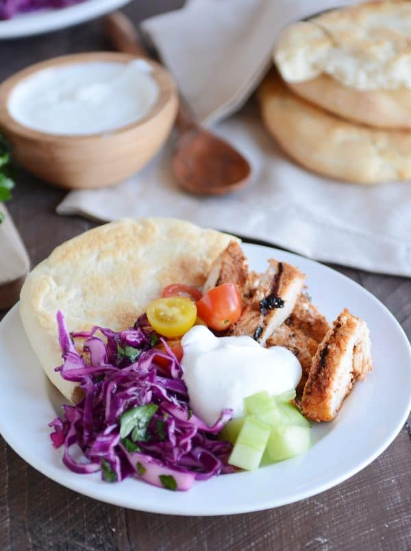White plate with slices of chicken shawarma, yogurt sauce, flatbread and vegetables.