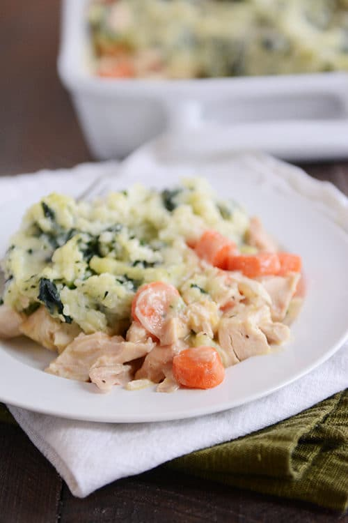 a creamy chicken and vegetable mixture next to kale-filled mashed potatoes.