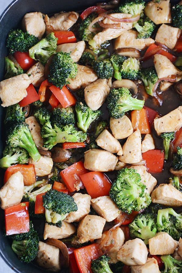 Top view of a skillet of cooked chicken, broccoli, peppers, and onions.