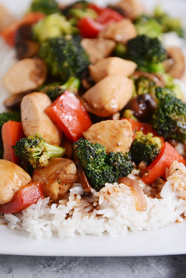 Chicken and vegetable stir-fry over cooked white rice.