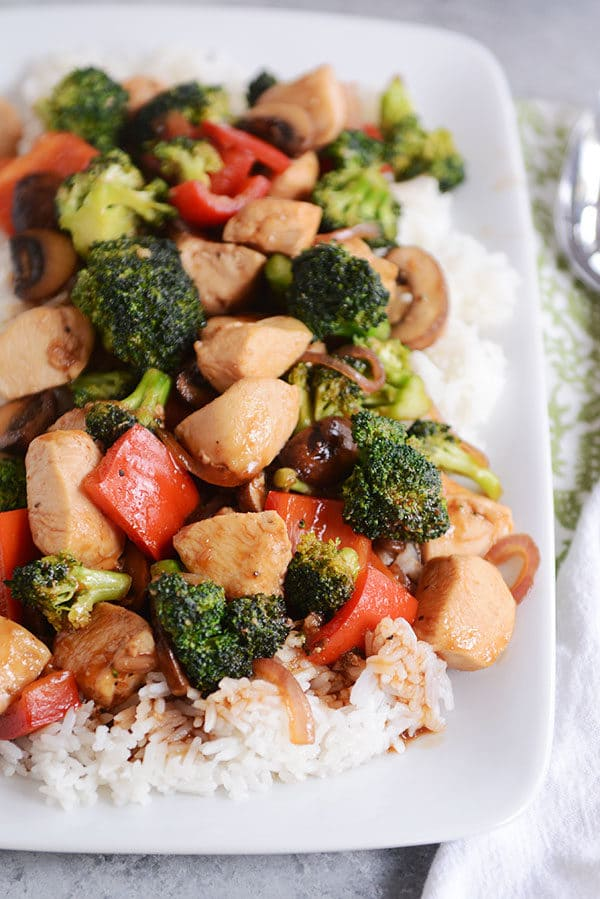 Top view of a white platter of cooked white rice topped with chicken and vegetables.