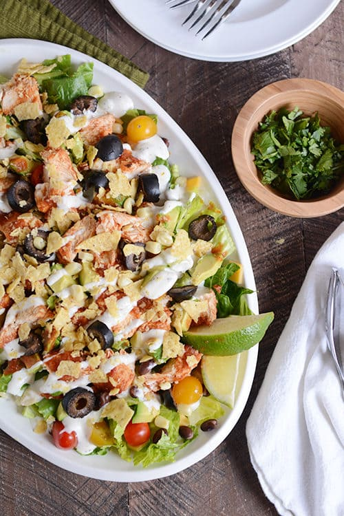 A white oval bowl full of a chicken taco salad drizzled with dressing.