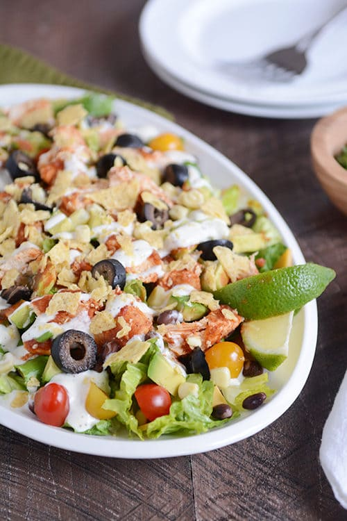 A large bowl with a chicken taco salad loaded with toppings and drizzled with dressing.