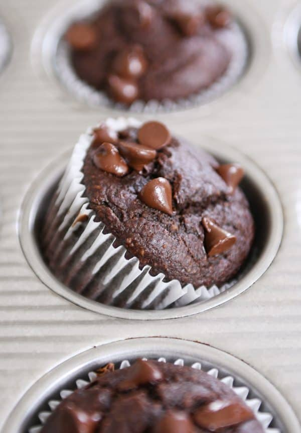 Double chocolate banana blender muffin propped on side in metal tin.