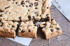Slab of chocolate chip cookie bars cut into pieces.