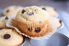 Easy one-bowl chocolate chip muffin unwrapped sitting on top of muffin tin.