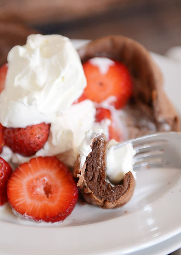 A fork taking a bite out of a chocolate pancake that is covered in whipped topping and sliced strawberries.